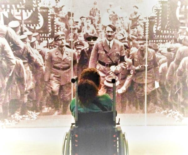 Ragazza in carrozzina davanti a una fotografia di Hitler