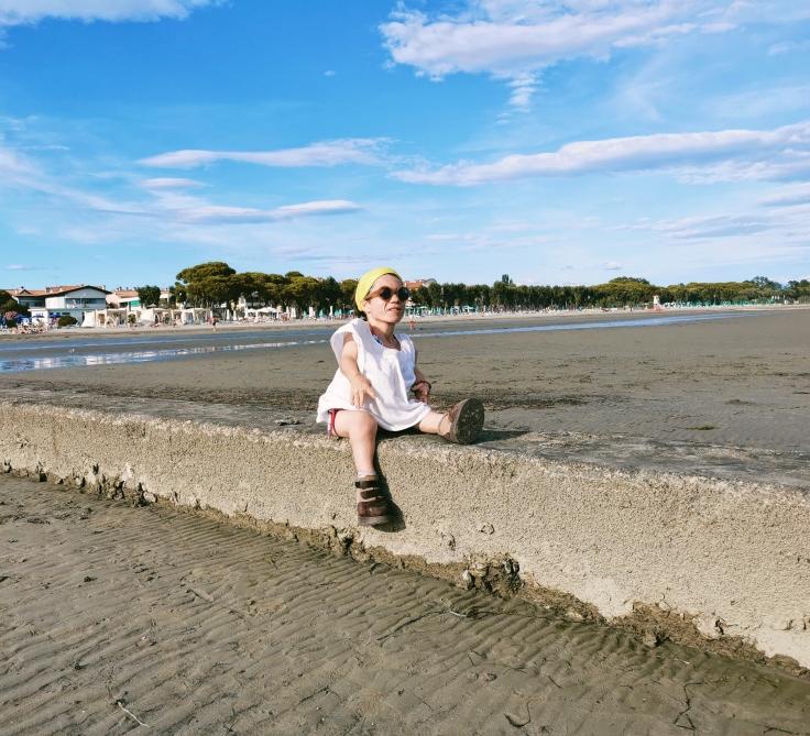 Nanabianca seduta su un muretto sulla spiaggia di Grado